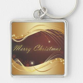 Chaveiro Motriz dourado do Natal com fundo vermelho…