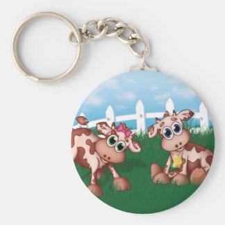 Chaveiro Vacas do bebê em um lado do monte com da cerca