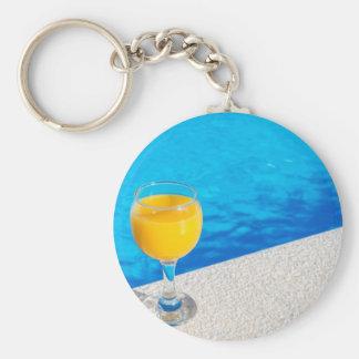 Chaveiro Vidro com sumo de laranja na borda da piscina
