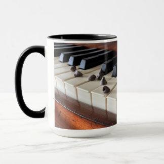 Chaves do piano e caneca dos pedaços de chocolate