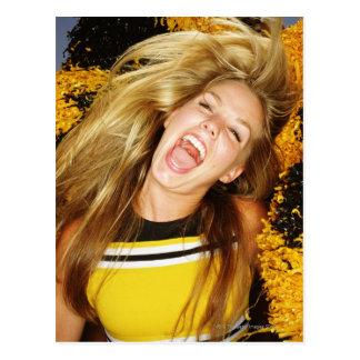 Cheerleader que lança o cabelo, rindo, cercado cartao postal