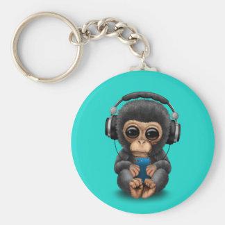 Chimpanzé do bebê com fones de ouvido e telemóvel chaveiro