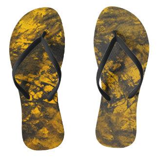Chinelos De tinta preta no fundo amarelo