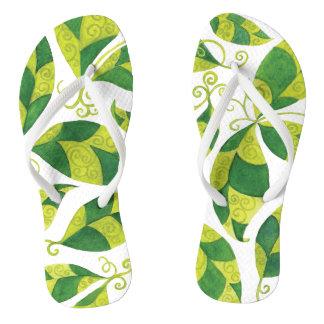 Chinelos finos da correia com as folhas verdes