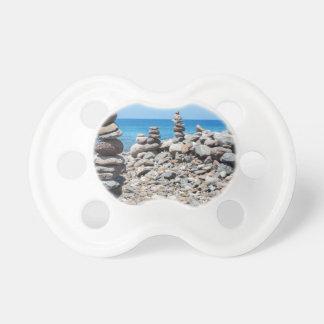 Chupeta Pedras empilhadas da praia no mar azul