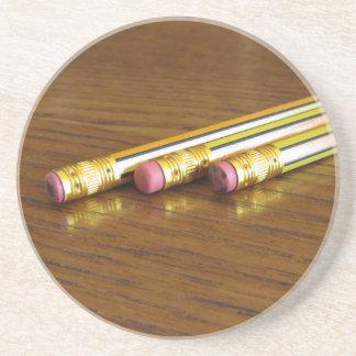 Close up de eliminadores de lápis usados na mesa porta copos de arenito