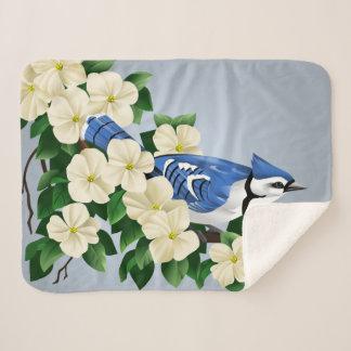 Cobertor Sherpa Jay azul entre flores do Dogwood