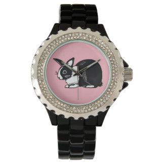 Coelho holandês preto e branco com relógio de