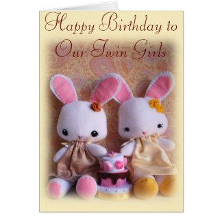 Coelhos gêmeos com o cartão do feliz aniversario d