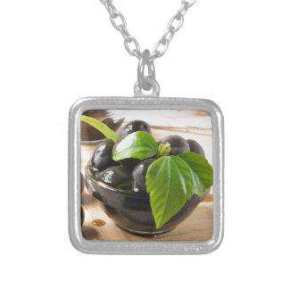 Colar Banhado A Prata Azeitonas pretas em uma mesa e em copos do vidro