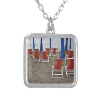 Colar Banhado A Prata Cadeiras de madeira coloridas na praia da areia