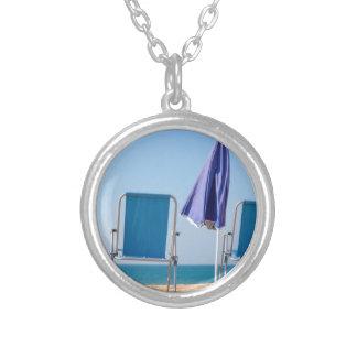 Colar Banhado A Prata Dois cadeiras e parasóis azuis de praia em sea.JPG