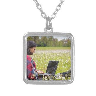 Colar Banhado A Prata Mulher que senta-se com o laptop no prado do