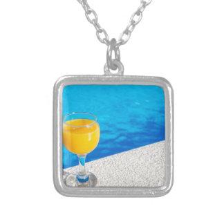 Colar Banhado A Prata Vidro com sumo de laranja na borda da piscina