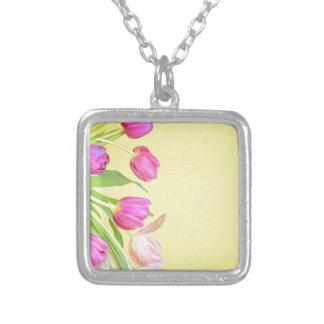 Colar Banhado A Prata Vista às tulipas coloridos sobre o papel amarelo