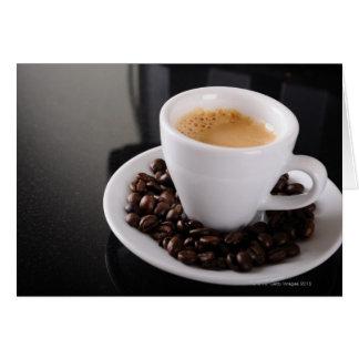 Copo do café no contador preto do granito cartões