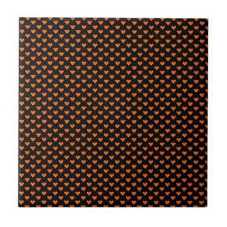 Corações alaranjados no preto azulejos de cerâmica