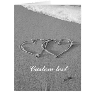 Corações de bloqueio em cartões da areia da praia