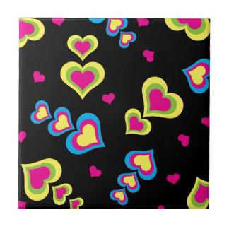 Corações de néon no preto azulejo
