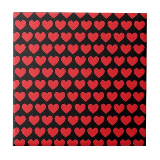 Corações vermelhos minúsculos no preto azulejo