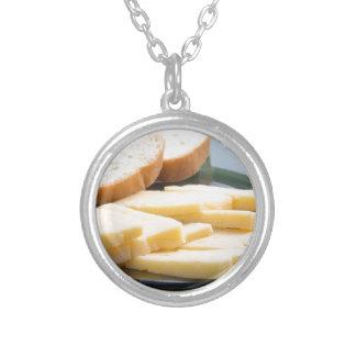 Corte fatias de queijo em um fim-acima da placa colar banhado a prata