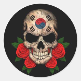 Crânio coreano sul da bandeira com rosas vermelhas adesivo redondo
