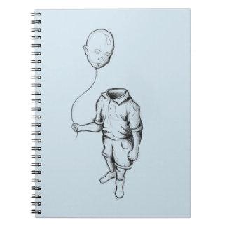 Criança com um caderno do balão