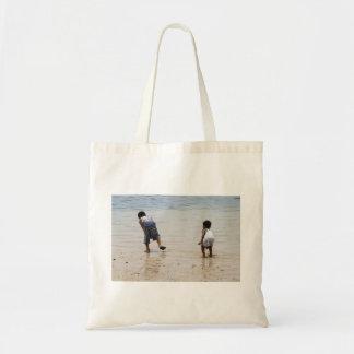 Crianças que jogam na praia bolsas para compras