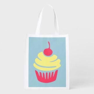 Cupcake cor-de-rosa e amarelo com a cereja na sacola ecológica