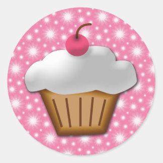 Cupcake do entalhe com a cereja cor-de-rosa na adesivo em formato redondo
