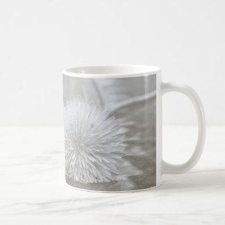 Dentes-de-leão de flutuação na caneca de café da