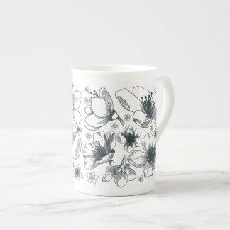 Desenho da flor na caneca da porcelana de osso