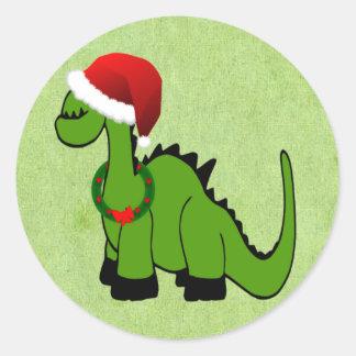 Dinossauro verde em um chapéu do papai noel para o adesivos em formato redondos