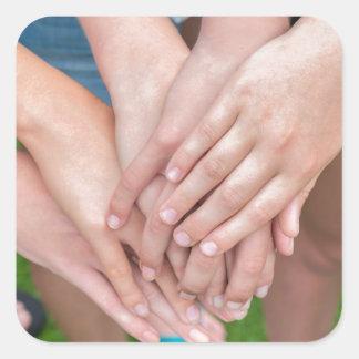 Diversos braços das meninas com cedem-se adesivo quadrado