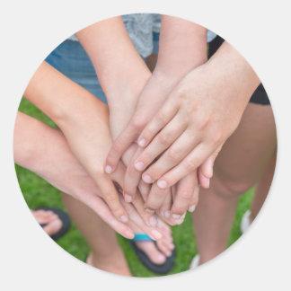Diversos braços das meninas com cedem-se adesivo redondo