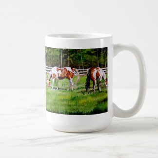 Dois cavalos da pintura que pastam canecas