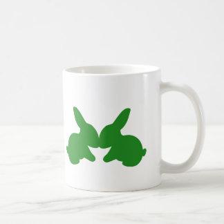 Dois coelhos que beijam em uma caneca de café