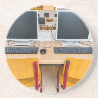 Dois computadores na sala de aula no segundo grau porta-copos de arenito