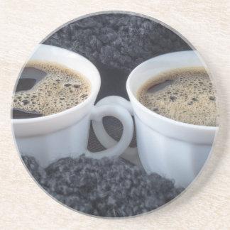 Dois copos brancos com café preto e espuma porta-copos de arenito