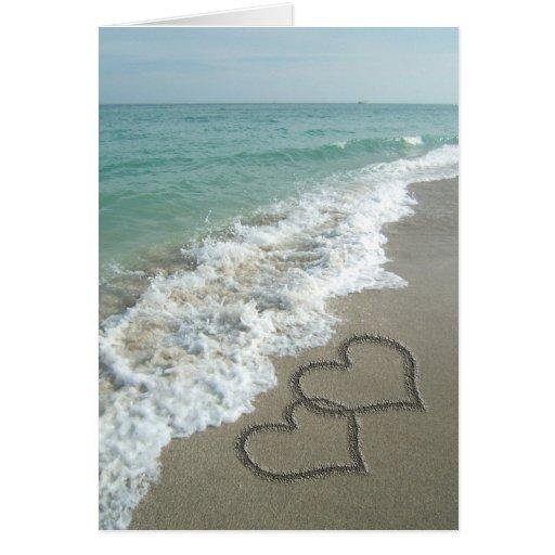Dois corações da areia na praia, oceano romântico cartão