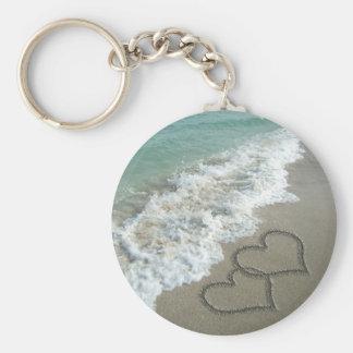 Dois corações da areia na praia, oceano romântico chaveiro
