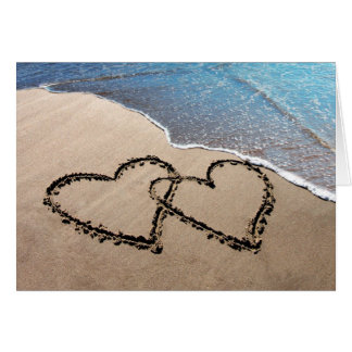 Dois corações no cartão da areia