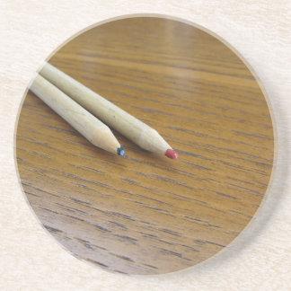 Dois lápis coloridos usados na mesa de madeira porta copos de arenito