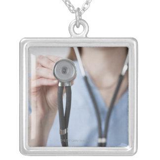 Doutor fêmea de sorriso com estetoscópio colar com pendente quadrado