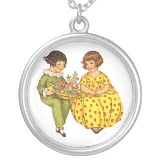 Duas crianças com flores colar com pendente redondo
