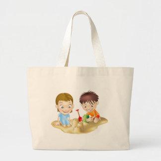duas crianças que jogam na areia bolsas