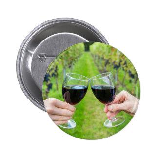 Duas mãos que brindam com vidros de vinho no bóton redondo 5.08cm