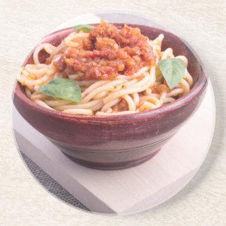 Espaguetes cozinhados em uma bacia de madeira porta copos de arenito