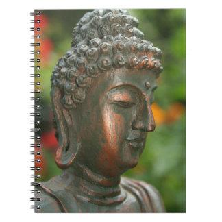 Estátua de Buddha com as flores no caderno do