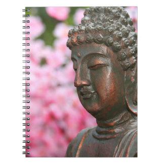 Estátua de Buddha com caderno das flores de